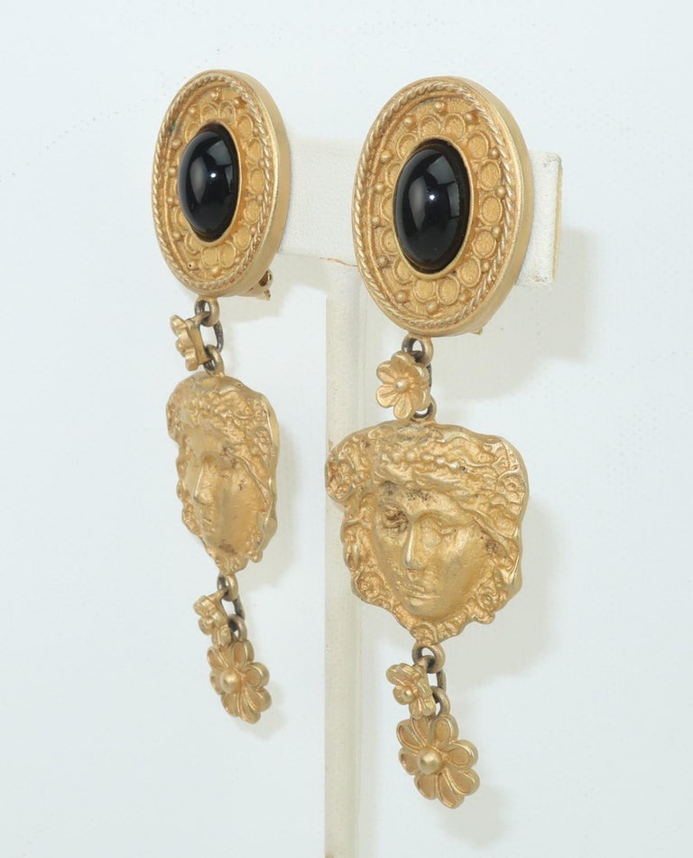 Mandy Dan brushed gold tone dangle earrings with an ancient Greek style design incorporating a Goddess and floral pattern.  The clip on base is accented with a black glass cabochon.  Signed at the back of each earring. CONDITION Good to fair