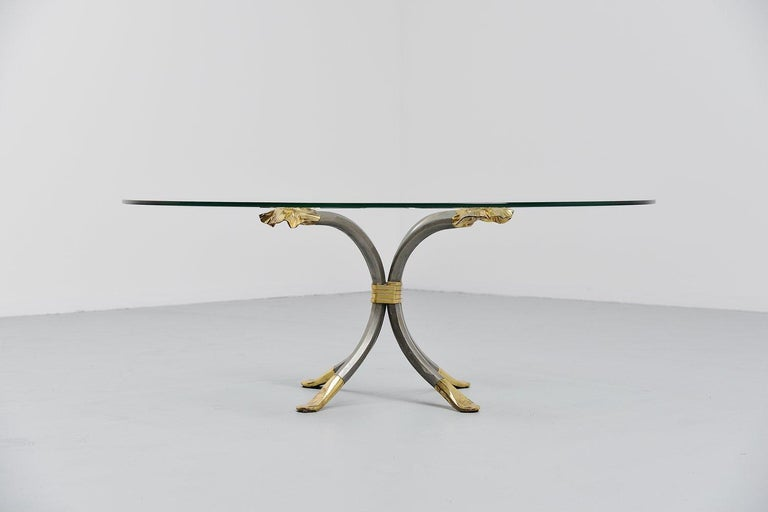 Very nice coffee table designed and made by the blacksmith Manfred Bredohl, Germany, 1970. This table has a lacquered iron base with brass details and an oval glass top. The table was stamped at one leg, Bredohl design. We have a pair of these