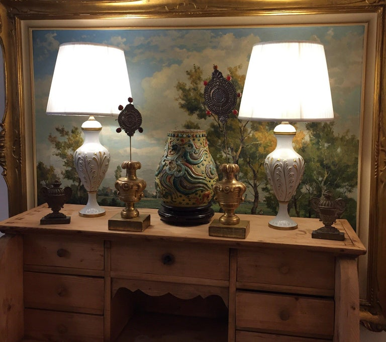 Pair of Italian porcelain table lamps manufactured by Mangani Firenze, circa 1980, good condition. Circular white porcelain bases with gold leafted decoration in relief, marked on the bottom with N dipinto a mano (hand painted). The porcelain base