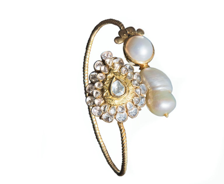 Styled with polkis (uncut diamonds) and natural baroque pearls set in 22k gold, attached to an 18k twisted wire bracelet. Polki(uncut diamonds) 1.5ct. Pearl 6ct. Baroque Pearl 20ct. Size: Adjustable. Centre piece is 28mmx24mm. Bracelet Gold twisted