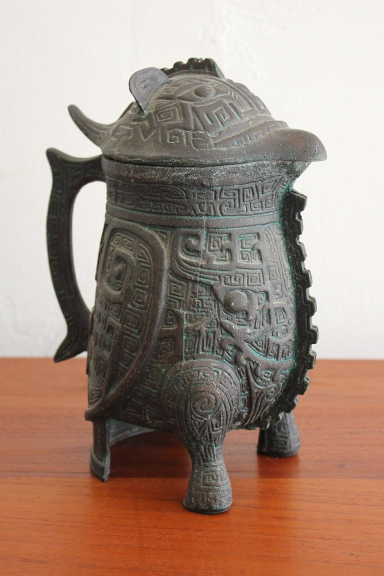 Great water pitcher in the manner of James Mont, circa 1960s. Has a Chinese/Asian design with a Verdigris finish. The water pitcher is in excellent shape with very light use over the years. Measures 7 1/2