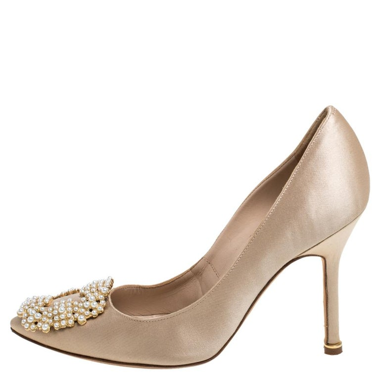These iconic pumps are by Manolo Blahnik. Styled in beige satin with dazzling pearl embellishments on the toes, and leather insoles to provide comfort, these luxurious pumps will never fail to lift your outfits. Complete with 10 cm heels, you can