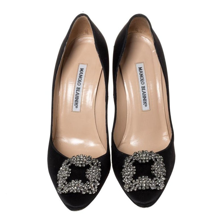 These iconic pumps are by Manolo Blahnik. Styled in black satin with dazzling embellishments on the toes, and leather insoles to provide comfort, these luxurious pumps will never fail to lift your outfits. Complete with 10 cm heels, you can wear