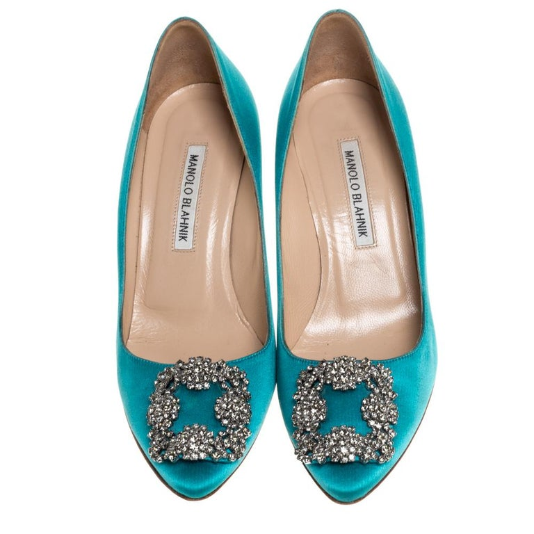 These iconic pumps are by Manolo Blahnik. Styled in blue satin, with dazzling embellishments on the toes, and leather insoles to provide comfort, these luxurious pumps will never fail to lift your outfits. Complete with 8 cm heels, you can wear them