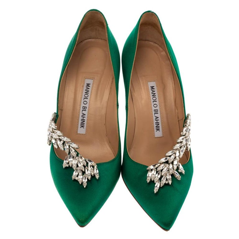 Allow this amazing pair of pumps by Manolo Blahnik to enliven your look. Crafted with emerald green satin, they are adorned with eye-catching Nadira embellishments and profiles adorable pointed toes. The leather-lined insoles carry brand labeling.
