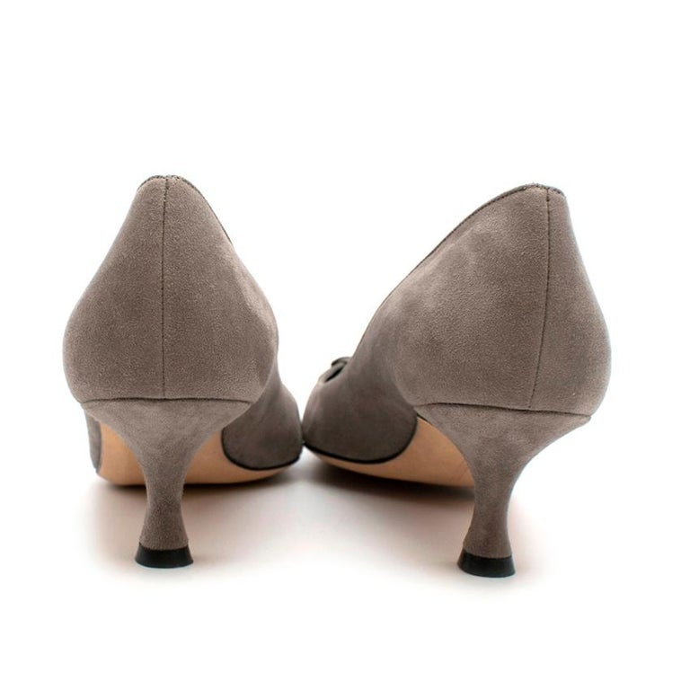 Manolo Blahnik Grey Suede Pumps    These grey suede pumps feature elegant layered flower detail atop an almond toe, bringing texture and romance to a clean design in smooth suede.  Handmade in Italy   Please note, these items are pre-owned and may