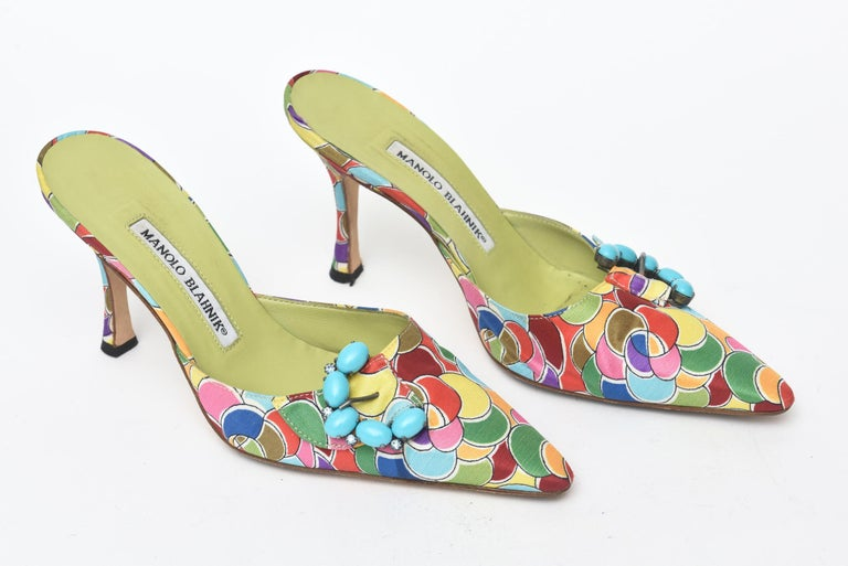 This gorgeous pair of Manolo Blahnik pair of sexy mules have the most luscious silk printed design on them with chartreuse leather interior. The design is very Pucci esque. The turquoise like stones in a half moon cluster on the side add dimension