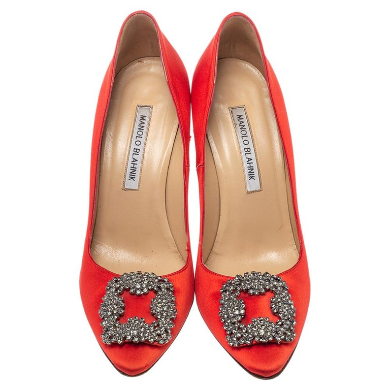 These iconic pumps are by Manolo Blahnik. Styled in red satin with dazzling embellishments on the toes and leather insoles to provide comfort, these pumps will never fail to lift your outfits. Complete with 10 cm heels, you can wear them with