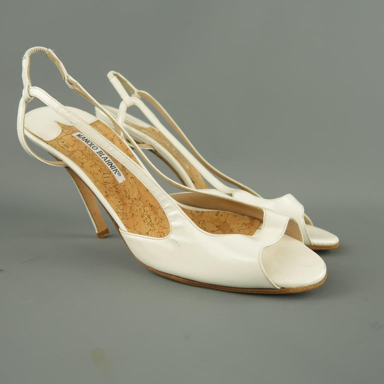 MANOLO BLAHNIK pumps come in white patent leather with a peep toe, covered stiletto heel, cork insole, and sling back. Resoled. Never worn but some marks from storage. As-is. Made in Italy.   Excellent Pre-Owned Condition. Marked: IT 42