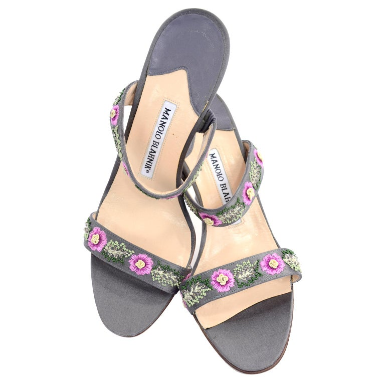 These pretty gray Manolo Blahnik shoes have beautiful embroidered pink flowers with cream centers and embroidered green leaves that are embellished with beading.  These open toe slide sandals have lovely heels and were only worn once.  Wear them in