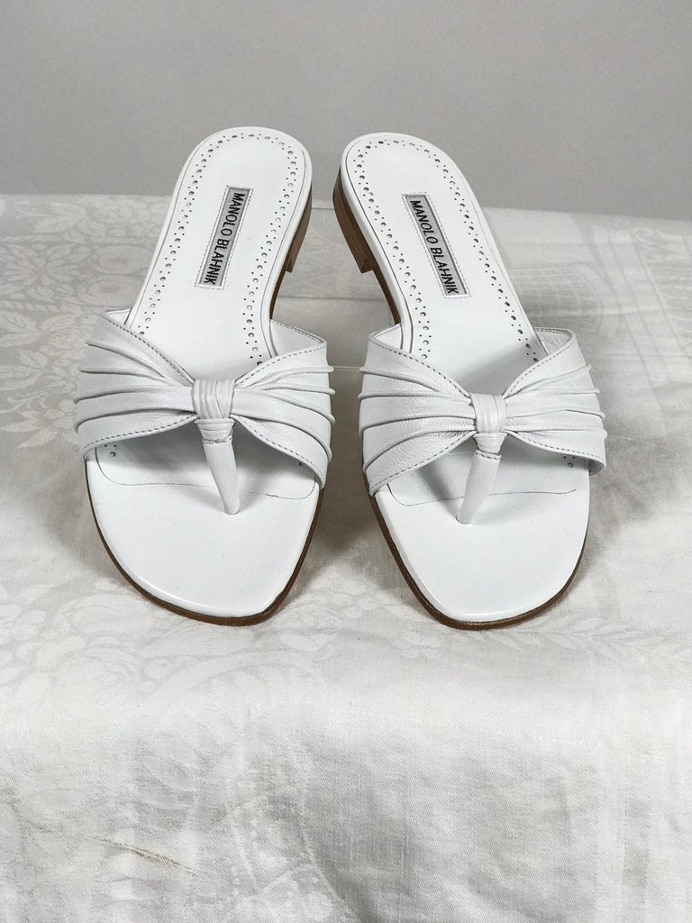 Manolo Blahnik white leather thong sandals unworn with box, size 7. The front sides are ruched white nappa leather, the shoes are all leather. Tagged price is $645. Protector bag included.