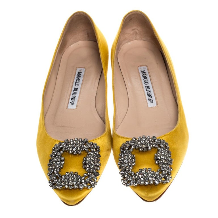 This stunning pair is from the iconic Hangisi collection of Manolo Blahnik. Made from smooth yellow satin, it features an almond toe and the signature crystal-jewelled buckle. These dainty flats will look elegant with any ensemble and exude charm on