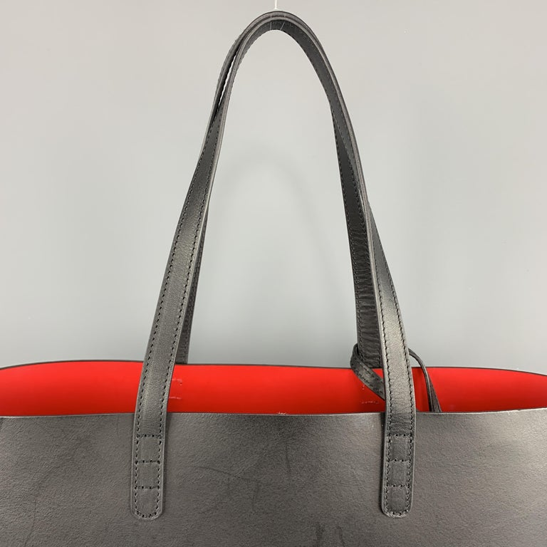 MANSUR GAVRIEL Tote bag comes in a smooth solid black leather, with a red interior, thin straps at drop, and a detachable wallet. Wear. Made in Italy.   Very Good Pre-Owned Condition.   Measurements: Length: 15 in. Width: 5.5 in. Height: 9.5