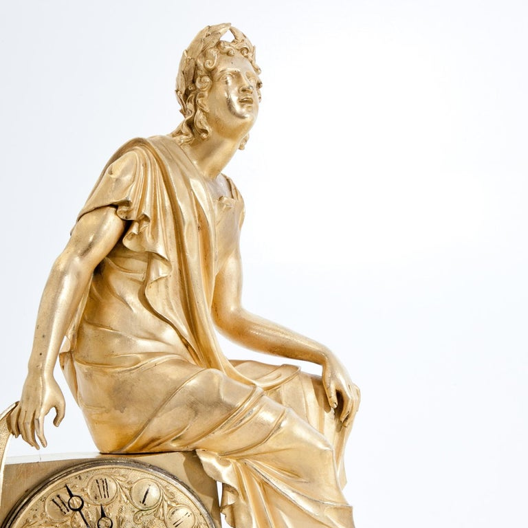 French gilt pendula clock with figurative depiction of Apollo with Kithara and a laurel wreath in his hair. At the rectangular base is a relief depicting numerous gods, like Zeus, Hera, Aphrodite and Hermes as well as Cerberus and the Moirai.