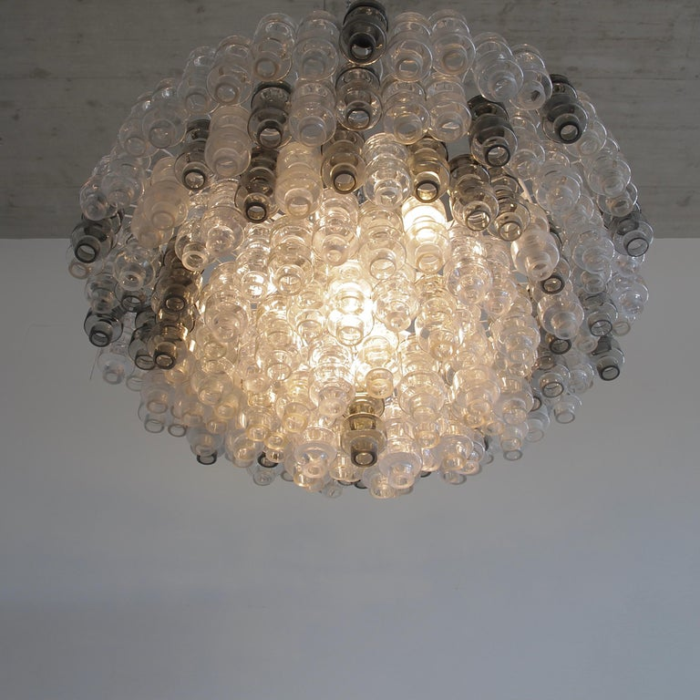 Large Manubri glass chandelier, Murano, Italy.  Chandelier with moulded 'Manubri' glass pieces in a variety of shades. Clear, slightly tinted and smoked glass pieces are available.  White metal structure, chrome chain and ceiling cover and well
