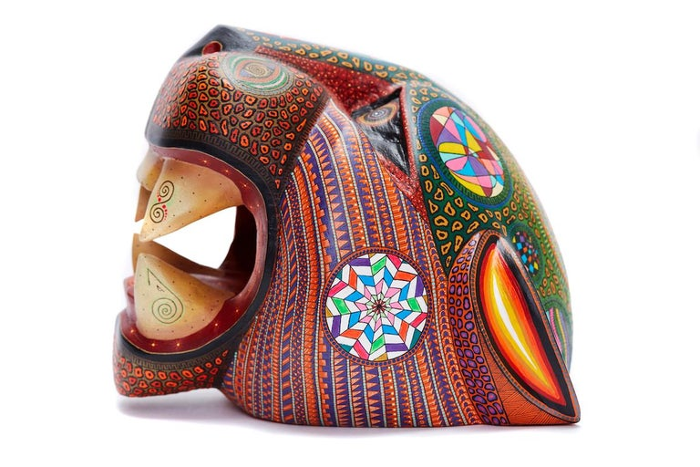 This Mexican Jaguar Mask was made with Copal wood, wood carving technique gouges, machete and sandpaper, decorated with natural dyes and acrylic paintings with Zapotec symbols. At Cactus Fine Art, we offer an exclusive selection of handmade items