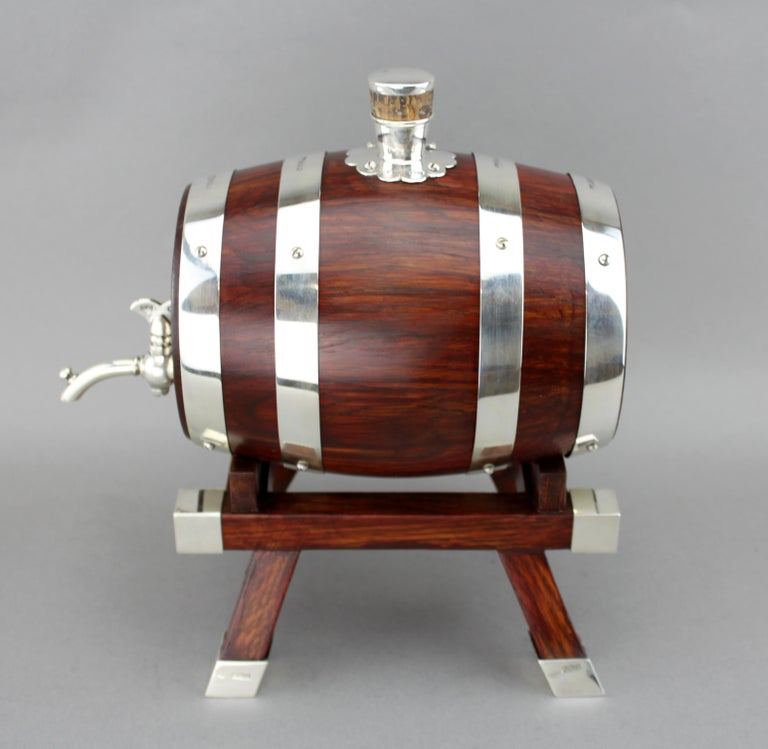 A sterling silver and wooden barrel / keg with tap for whiskey. Maker: Mappin & Webb Made in Birmingham, 1925 Fully hallmarked.  Dimensions: Size: 22.5 x 13.8 x 22.5 cm Weight: 1.5 kg  Condition: Keg is pre-owned, has some general usage