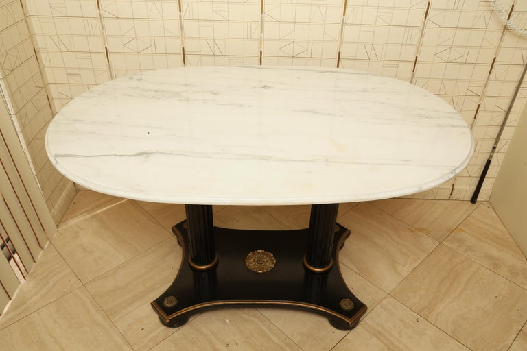 A sleek ovoid marble top on a high style neoclassical base makes a dynamic pairing. The base ebonized with gilt metal flowerhead mounts and gilt banding.