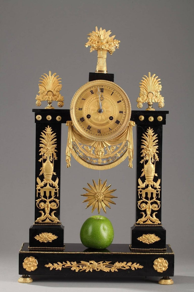 Portico clock in gilt bronze and marble, decorated with flower vases set above canopies, dolphins, and scrollwork. The sculpted, gilt clock face marks the hours in Roman numerals and is bordered with water leaf and small beads. It is set above an