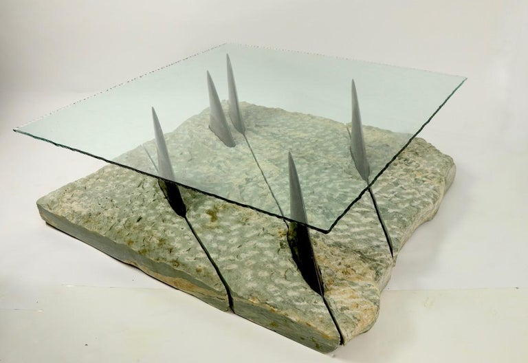 Incredible and probably unique table of marble and glass depicting a school of fish swimming in the ocean, with the fins protruding out of the water to support the glass top. The sea is composed of 4 sections of unpolished textured marble of sea