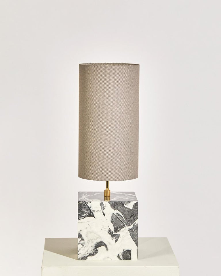 The Coexist table lamp consists of a marble cube base and a lampshade made from recycled fabric. The lamp serves as a sculptural centerpiece for any room, emitting a soft warm light to draw the viewer into the materials. The bold geometry of the