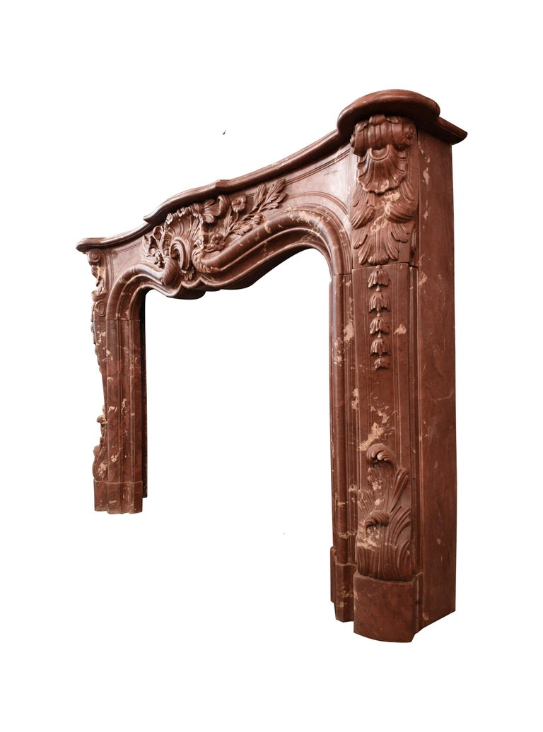 This marble/resin fireplace mantel is beautiful and heavy. The mantel has tones of red, pink and white. It is a luxurious and elegant decorative element - a lavish focal point in any living room. Ornate flowers and acanthus leaves dazzle from every