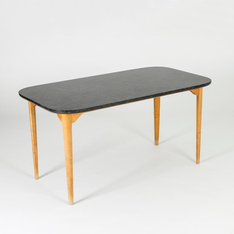 Coffee or playing table by Axel Larsson. Heavy black marble table top and birch base with an open and light look. Nice modernist design with a subtle traditional touch.