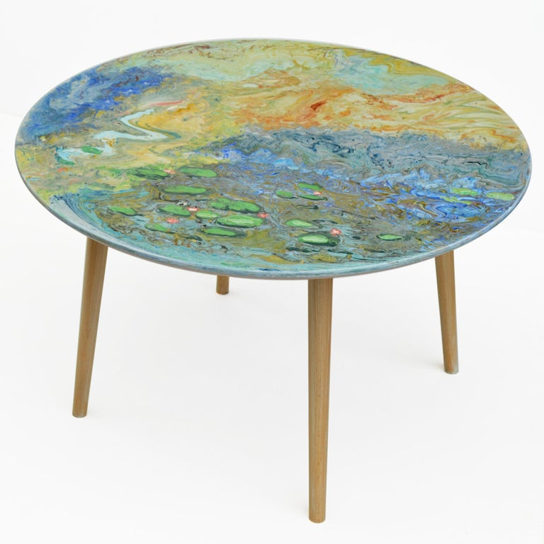 This small table made with marble top decorated entirely with scagliola art inlaies, whose decoration is a tribute to the French artist Monet and resumes its famous water lilies in a rather abstract vision. The base is made of natural wood with 4