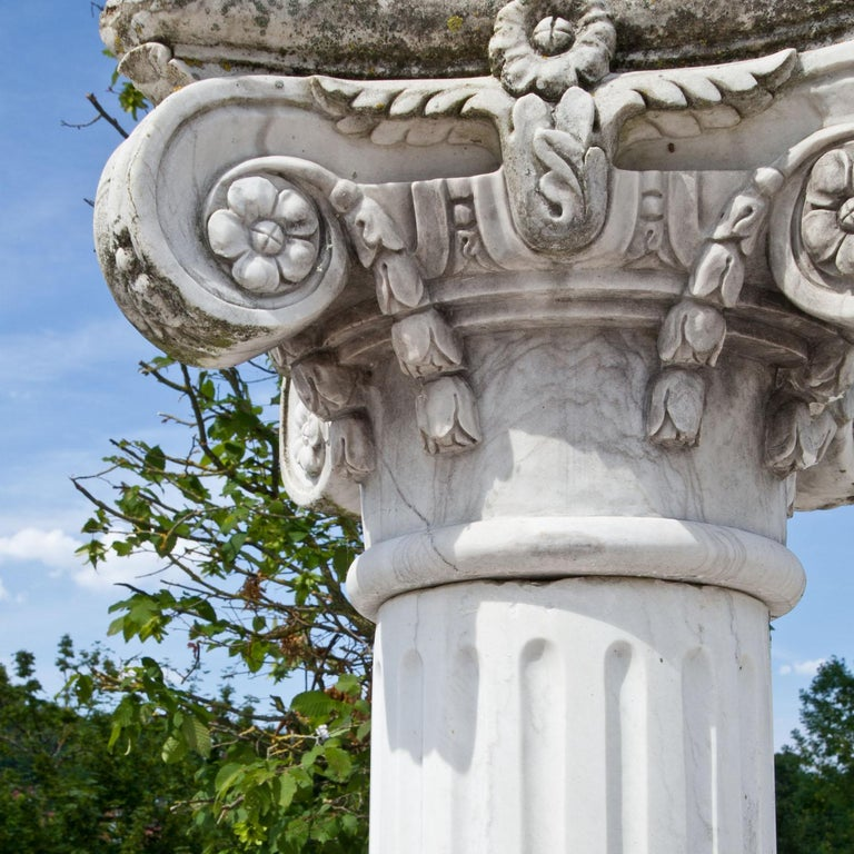 Tall column out of white marble and a naturally aged patina. The base is round, the shaft fluted and the capital with carved volutes and flower details.