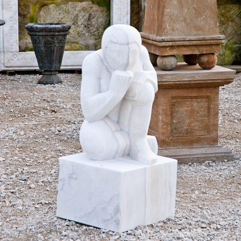 An abstract figure of a thinker squatting on a square pedestal, his chin resting on his fist. The sculpture is handcrafted from marble and has a fine surface structure.