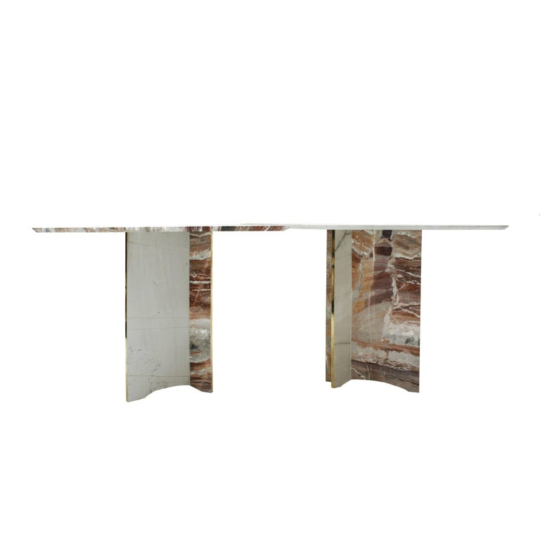 Dining table composed of two pieces of pink and white arabescato marble, and applications on brass top and feet.