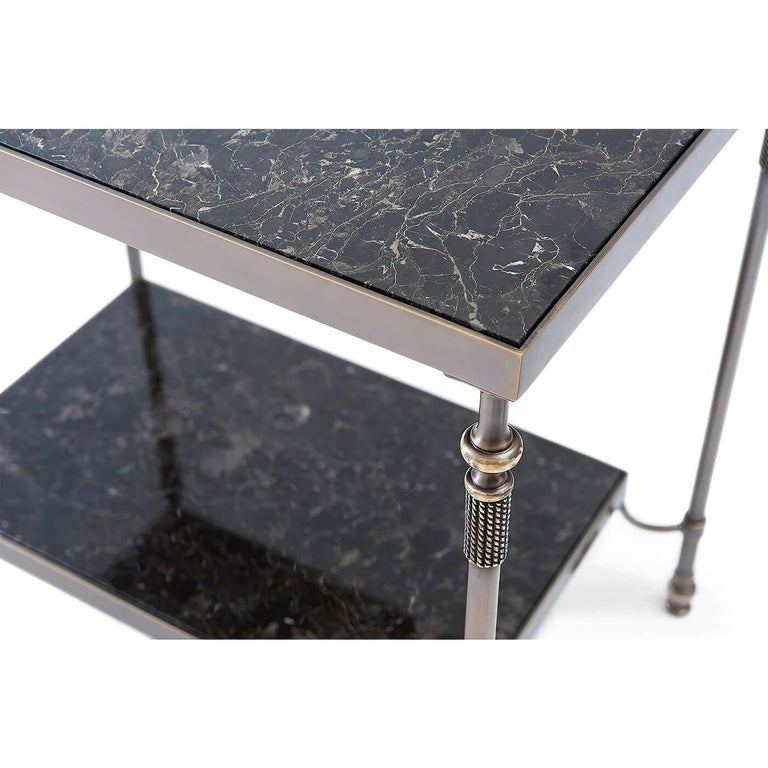 Modern brass and marble inset to tier table with an antique brass finish and Novo Portoro marble inset to the top and shelf stretcher  Dimensions: 28