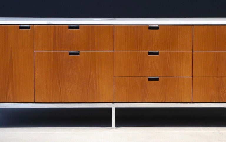 Simplicity in design. A stunning credenza designed by Florence Knoll for Knoll, featuring a marble top and tons of storage. Retains all six square metal leveling glides and pen drawer. Pictured with Harry Bertoia diamond chairs and side chair for