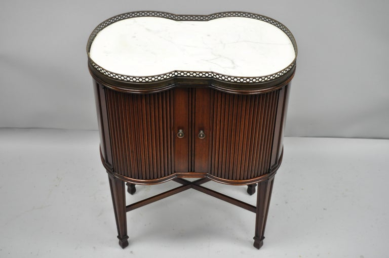 Marble-Top French Louis XVI Maison Jansen style bombe side table. Item features shapely bombe form, inset white shaped marble top, 2 swing doors, tapered legs, stretcher support, and pierced brass gallery, circa 1940. Measurements: 29