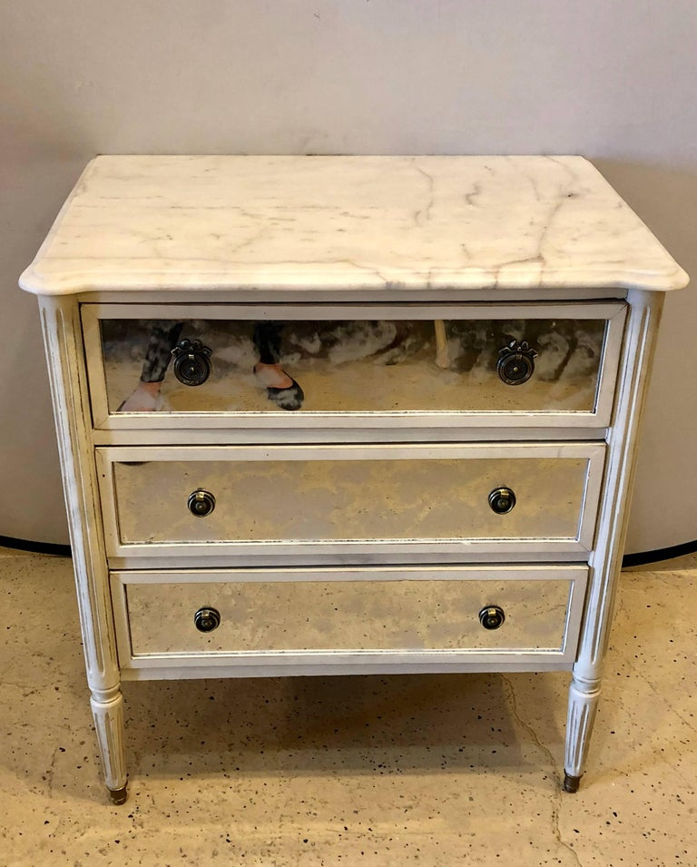 A Hollywood Regency style marble-top paint and Mylar decorated commode or nightstand in the Louis XVI style possibly by Maison Jansen.