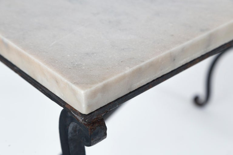 Marble top iron table, France, early 20th century. Original marble top on hand wrought iron base.