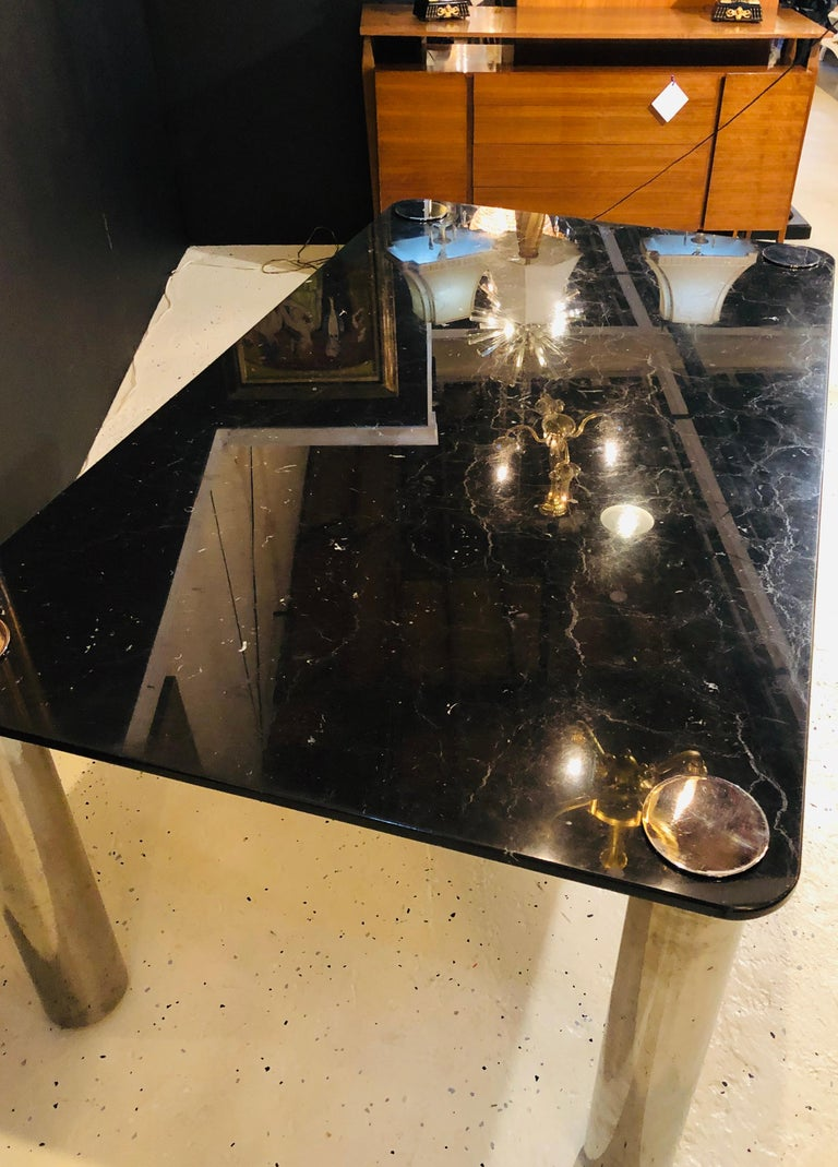 Marble-top Italian M.E.A dining / conference table. This finely crafted dining table holds the modern style to a higher standard. The solid black with gray and white veined marble top has the appearance of a moon light sky on four strong and strudy