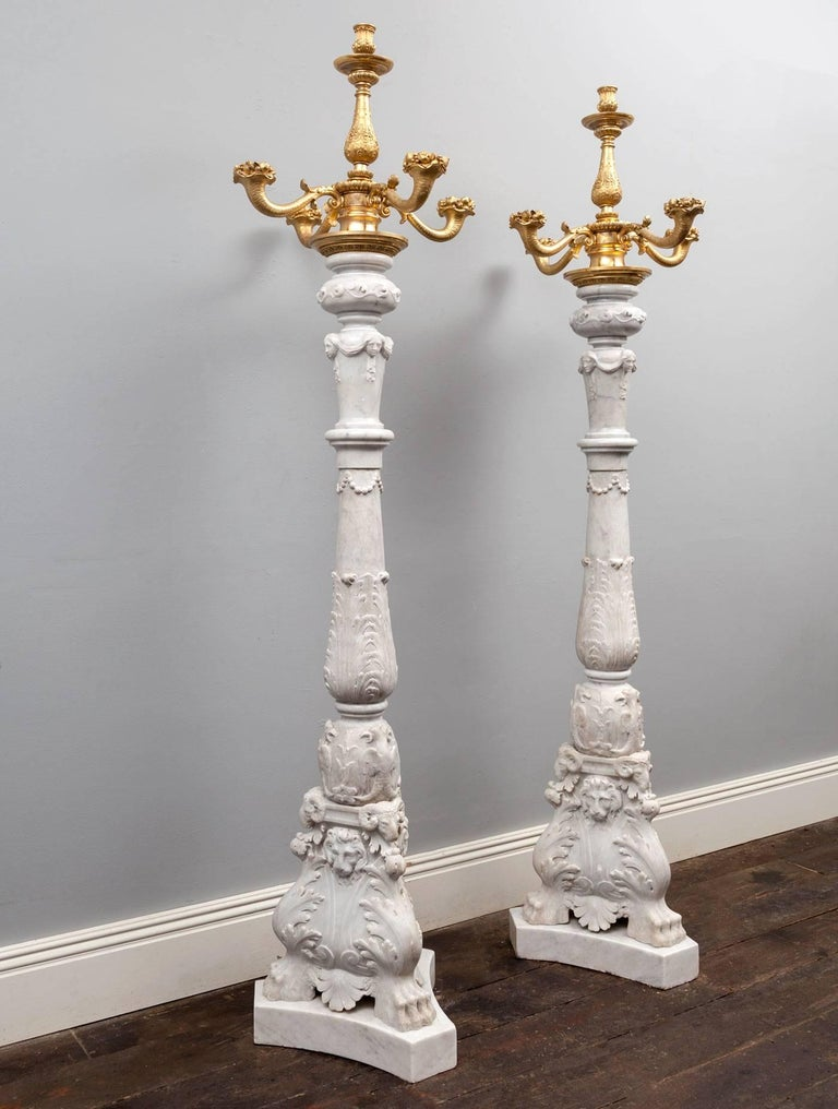 An exceptional pair of antique white Carrara marble and ormolu candelabra toucheres. Baroque in style and made during the 19th century in Venice, Italy.  The bases with hairy paw-feet, acanthus leaves, lions masks and rams heads. The baluster