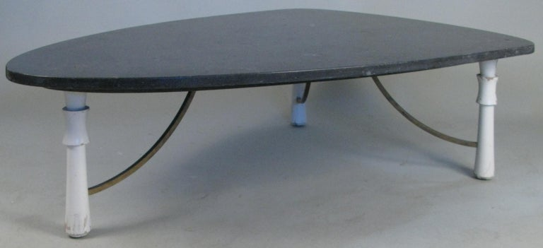 A beautiful 1950s triangular marble top cocktail table, with three leg base, the turned legs connected with brass supports. The dark grey marble top is in a triangle form with curved corners.