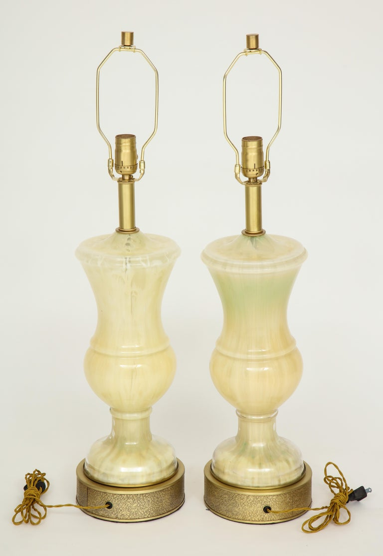 Pair of classical urn form Murano glass lamps in tones of cream and white on etched brass bases. Rewired for use in the USA. 100 W max. Glass body measures 17.5 inches tall.