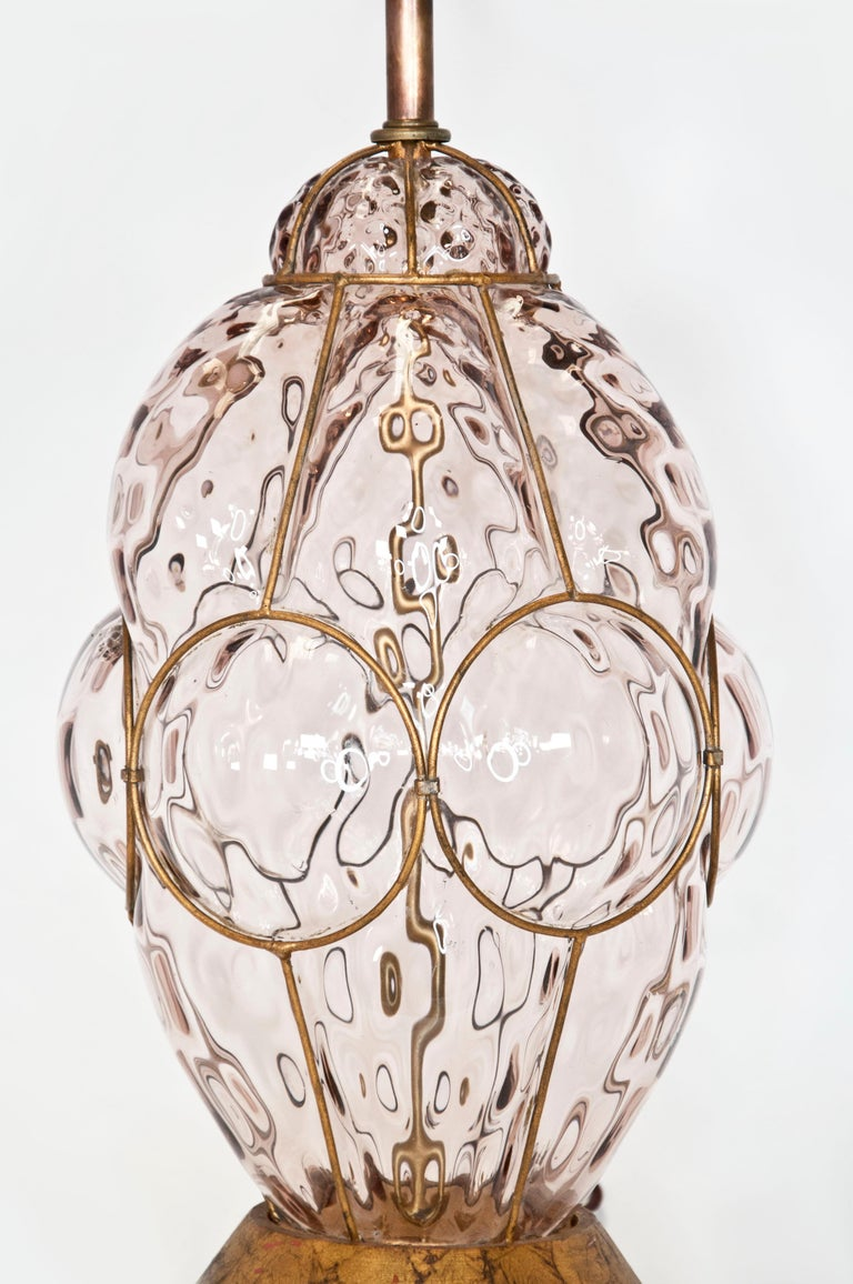 1960s Hollywood Regency Murano caged glass lamp by Marbro. Smoky topaz glass with a quilted diaper texture encased by an iron filigree cage. Original giltwood base. Cleaned and rewired. Finials match the finish on the bases.