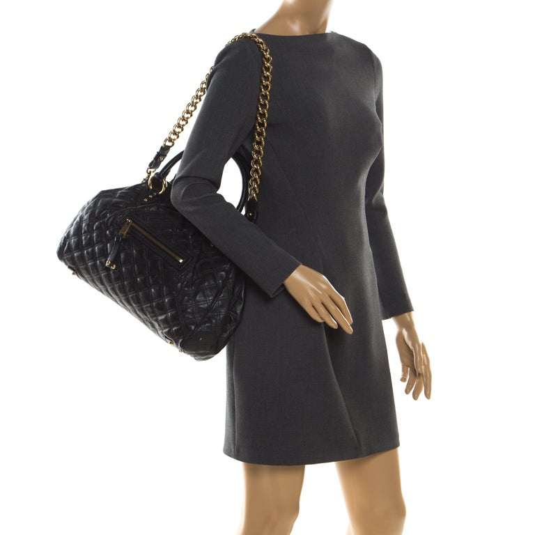 This Marc Jacobs design has a black quilted exterior crafted from Leather and enhanced with gold-tone hardware. This elegant Stam bag features a kiss-lock top closure that opens to a fabric interior, dual top handles and a removable chain that