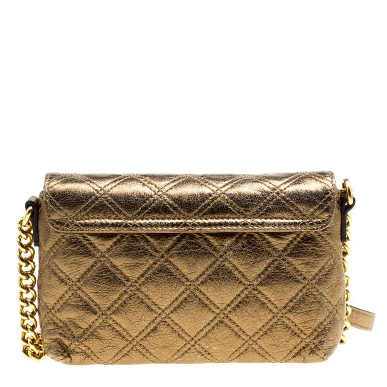 This Marc Jacobs Day To Night crossbody bag can be carried during the day or night, as the name suggests. Crafted from bronze leather, this bag features a quilted exterior and a push lock detail on the flap. It is held by a shoulder strap. Its