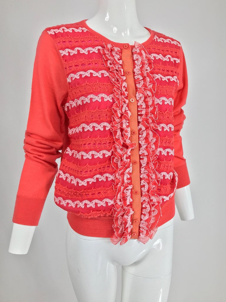 Marc Jacobs orange knit collage cardigan sweater. Long sleeve sweater with ribbed neck, hem and cuffs, the sweater front is done in panels of lace, knit and tulle, with tulle ruffles at either front side, like a collage of sorts. The sweater closes