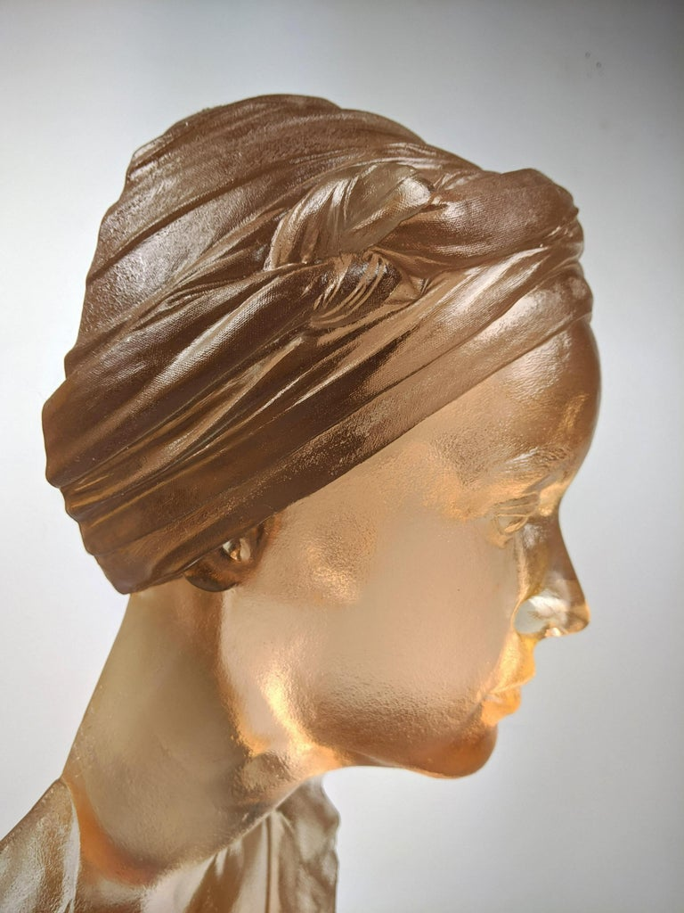 A cast acrylic sculpture titled Chin Up by American artist Marc Sijan. This sculpture is made from acrylic and portrays the upper torso of a clothed woman wearing a bandana over her free-flowing hair. Her eyes are closed and her head is tilted up as