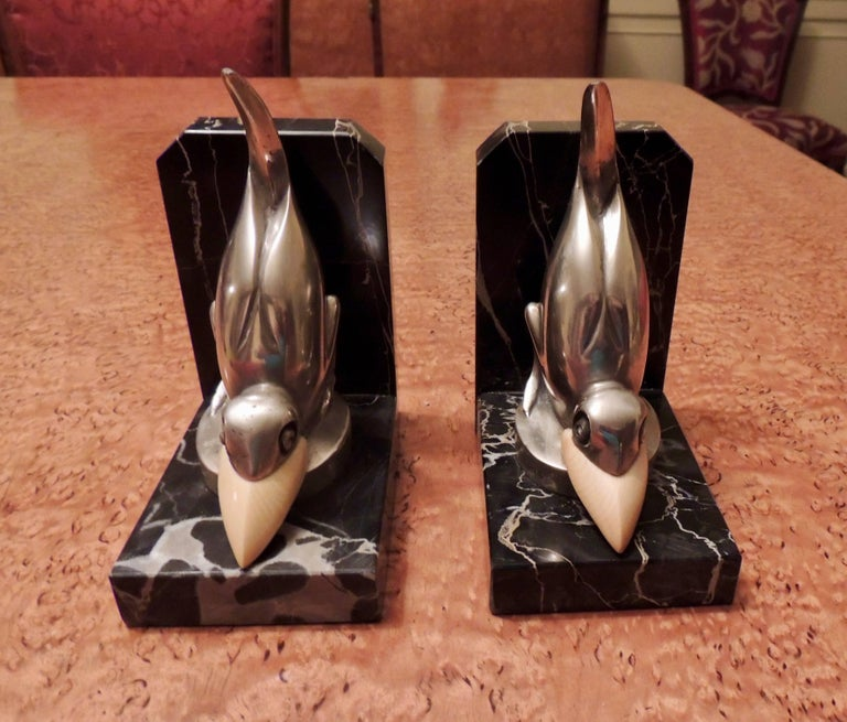 """These Art Deco bookends by Marcel Bouraine are playful pieces made of silvered bronze and mounted on Portoro marble. They are signed in the circular base M.Bouraine. This figure was also produced as a fancy automobile """"mascot"""", to be affixed to the"""