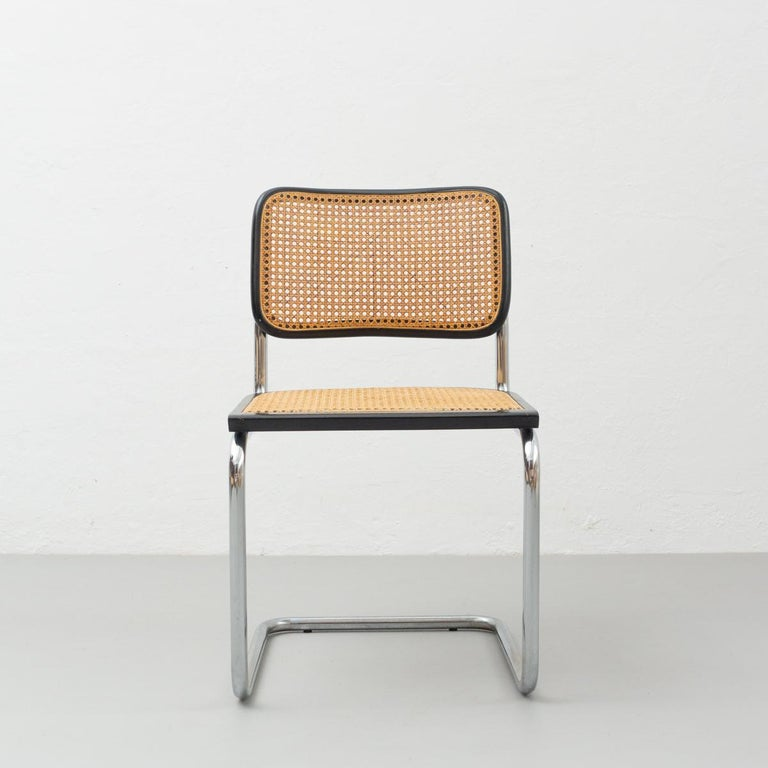 Chair model Cantilever, designed by Marcel Breuer circa 1960, by unknown manufacturer. Metal pipe frame, wood seat and back structure and rattan.  In original condition, with minor wear consistent with age and use, preserving a beautiful patina.