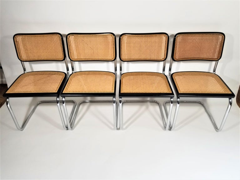Set of 4 Marcel Breuer Cesca side chairs with black finish. Cane seats and backs. Classic chrome cantilever frames. We polish all chrome.