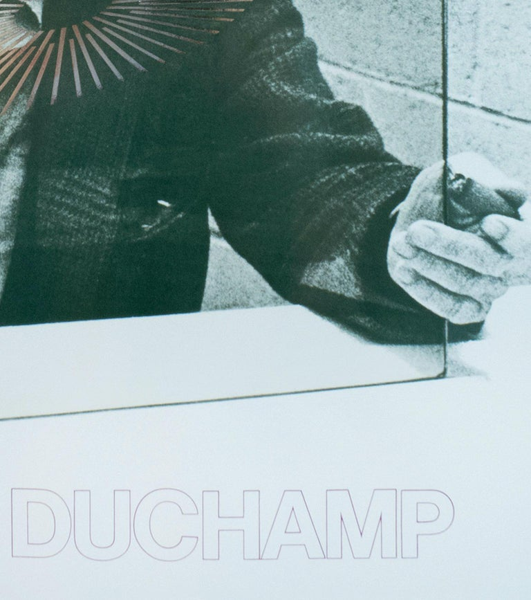 "This poster features a photograph, taken by Richard Hamilton, of Marcel Duchamp signing ""The Oculist Witnesses"" 1967 glass. The poster is an offset lithograph, with a clear polyester laminate which depicts the glass, and  embossed foil reproducing"