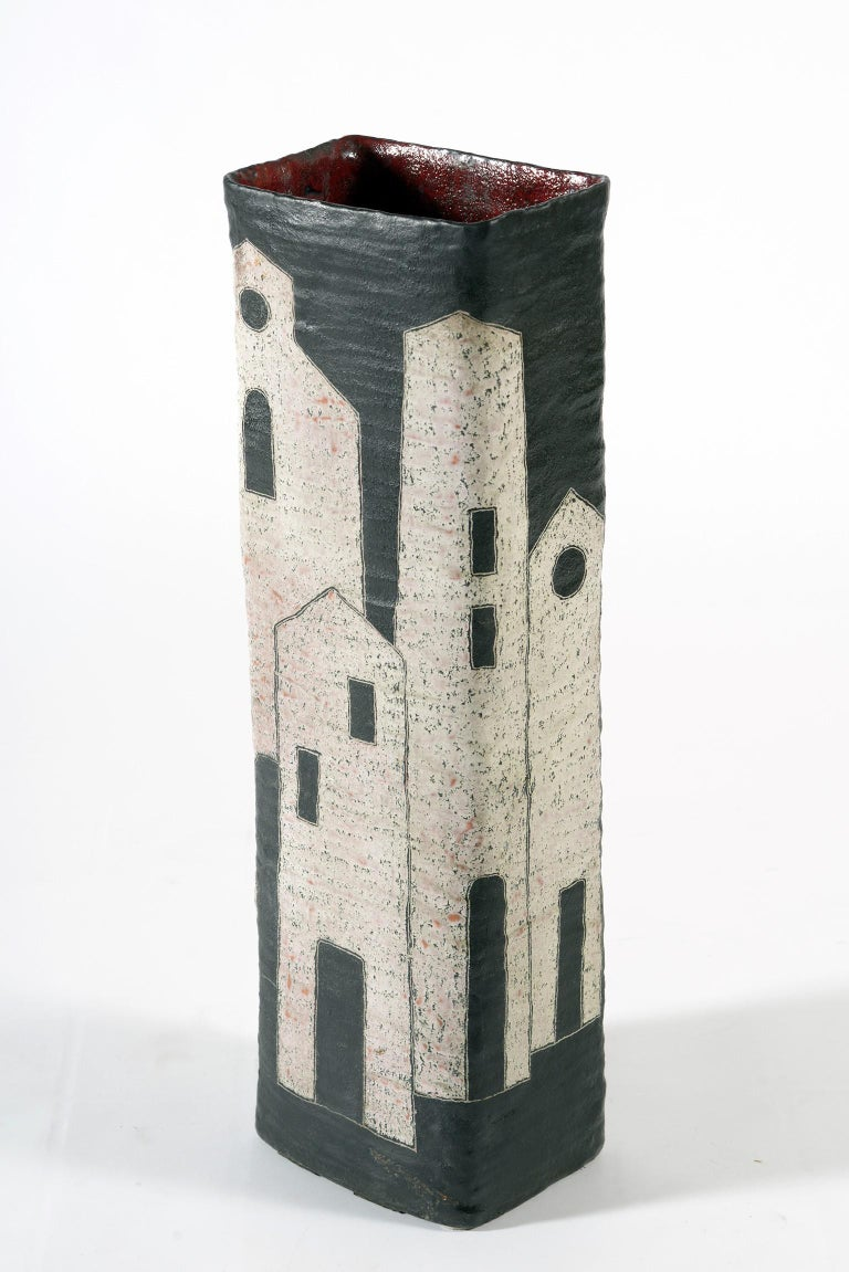 Large ceramic vase by master ceramist Marcello Fantoni Florence Italy from the 1950s, double decoration on one side of opaque black and white houses on the other side colored characters in glossy enamel. Inside this vase is red. Signed lower left